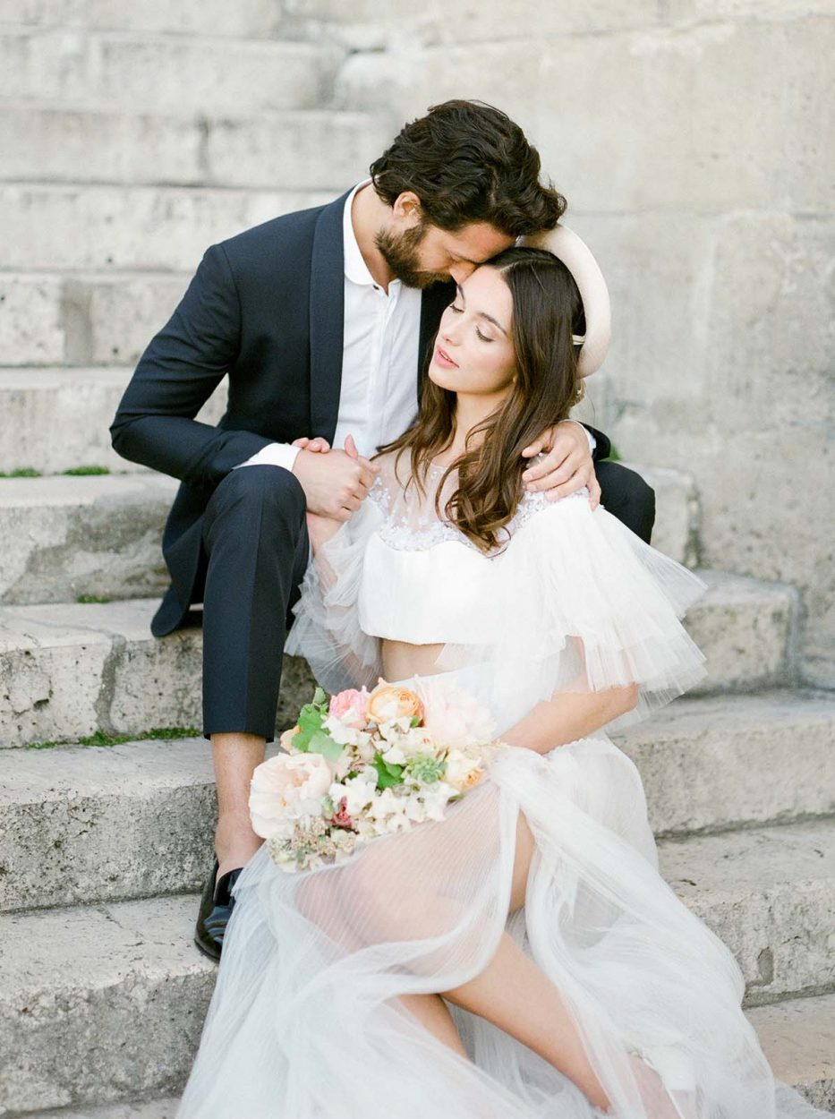 a wedding couple sitting on stairs holding a bouquet